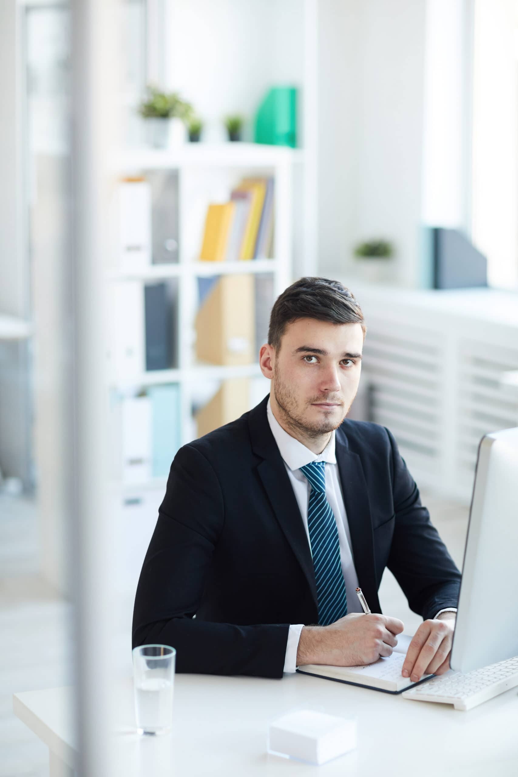 Contemporary young office worker sitting by desk in front of computer and writing down working plan in notebook