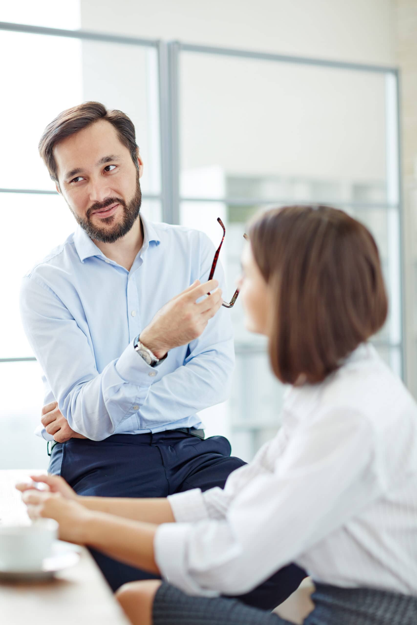 Confident businessman communicating with his partner at office